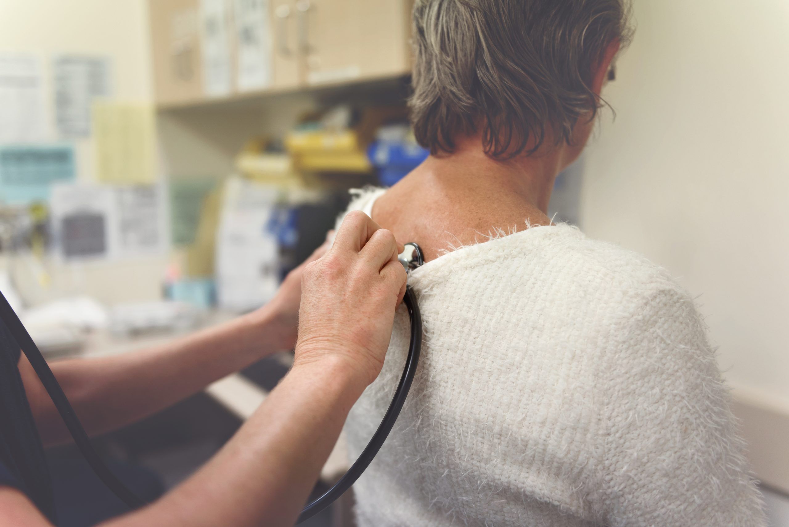 Medical professional using stethoscope on woman's back