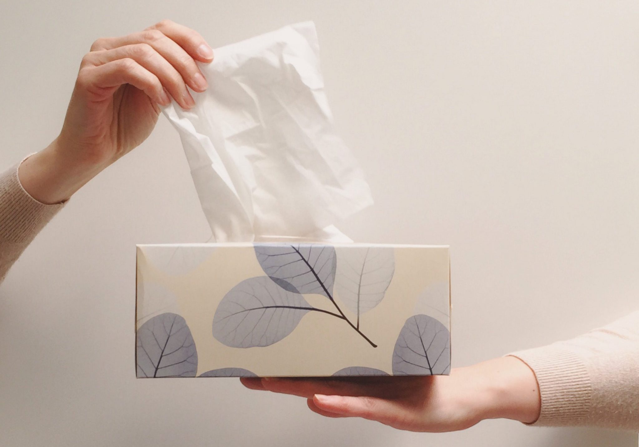 Hand taking tissue from a box