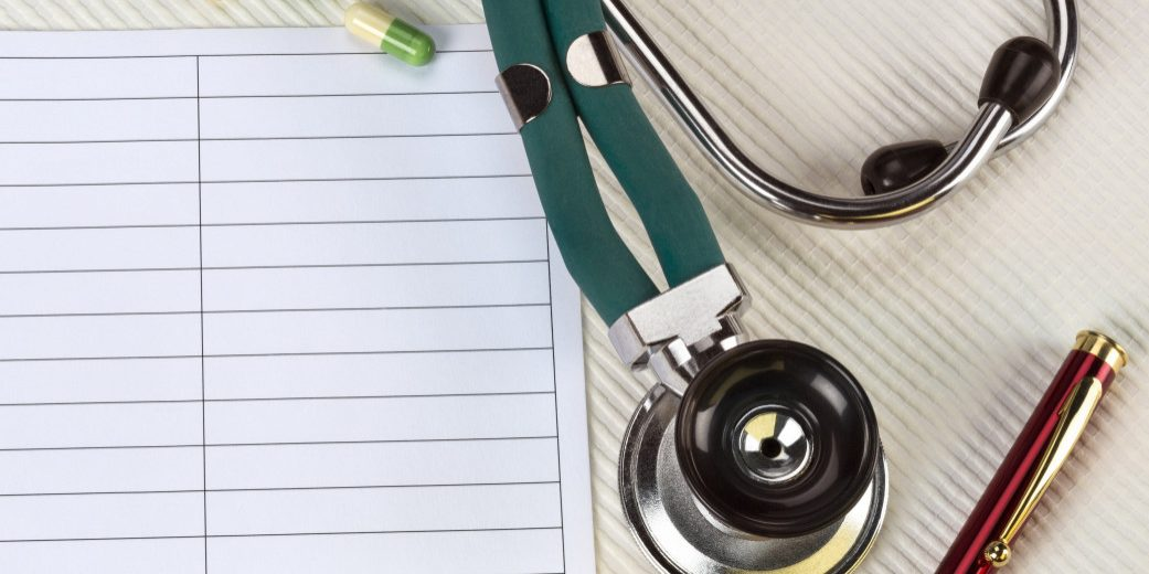 Stethoscope on desk with paper and pen