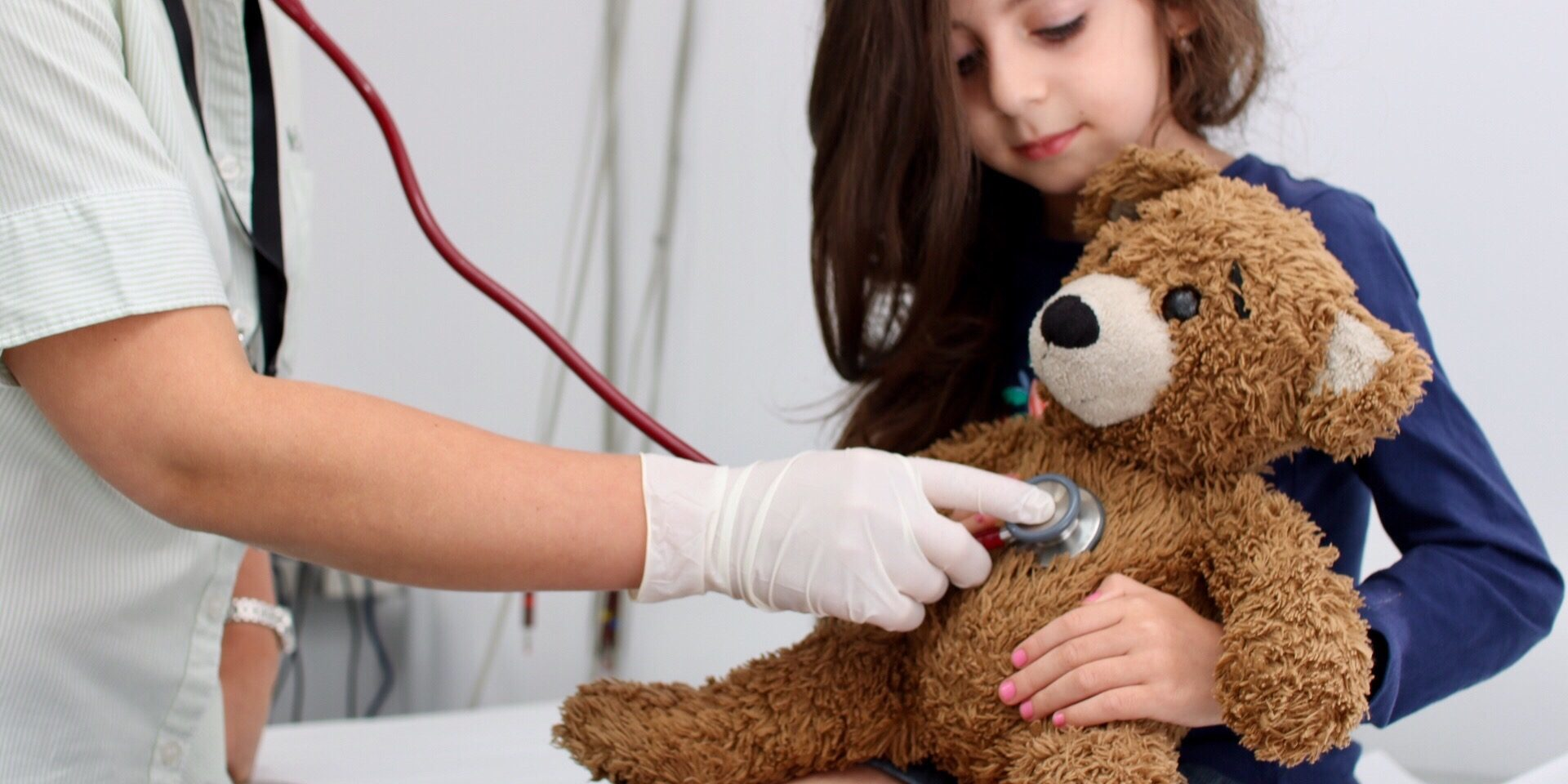 Medical professional using stethoscope on teddy bear in little girl's arms